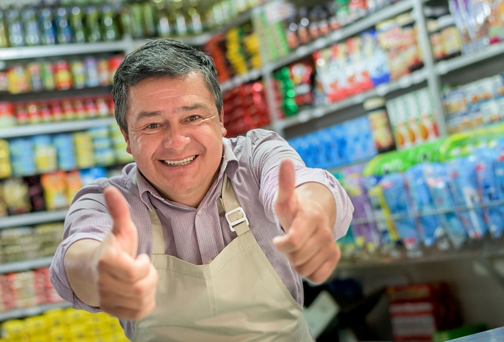 Successful shopkeeper at a local food shop with thumbs up looking very happy