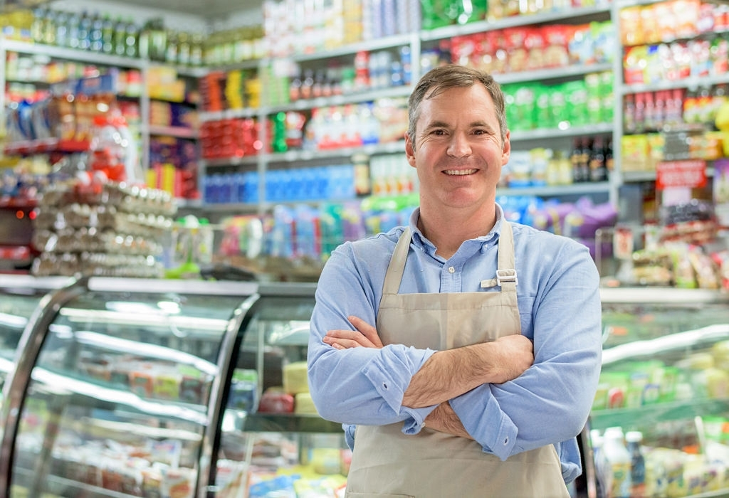 Happy business owner at a local store looking at the camera smiling with arms crossed